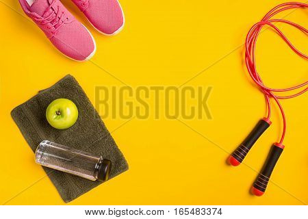 Athlete's set with female clothing, skipping rope and bottle of water on yellow background. Top view. Still life