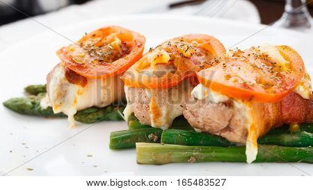 Bacon wrapped chicken breast with asparagus and tomato