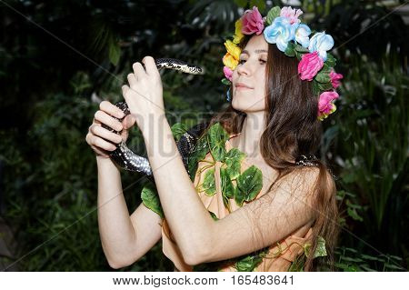 Young girl with floral wreath on her head holding a snake in his hands. Foliage forest on dark background.