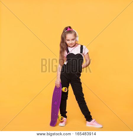 Little school girl posing with skateboard and headphones in the studio. Full body size portrait of long hair kid wearing modern casual clothes isolated on yellow background
