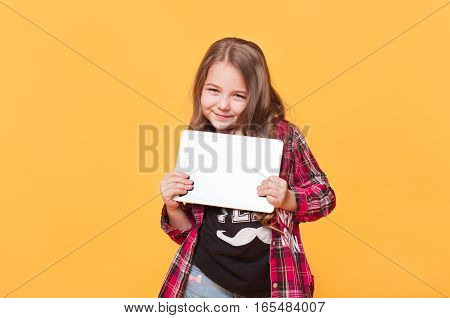 Stylish Cute Child with tablet computer. Little happy girl wearing casual modern clothes showing blank white screen isolated on yellow background