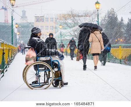 UZHGORODUKRAINE - JANUARY 04 2017: Poor man in wheelchair begging for alms in the street of Uzhhorod Ukraine