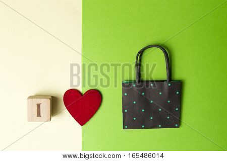 Retail, sale, I love shopping, concept with colorful shopping bag, red heart and wooden block against greenery and yellow background. Top view. Copy space for text