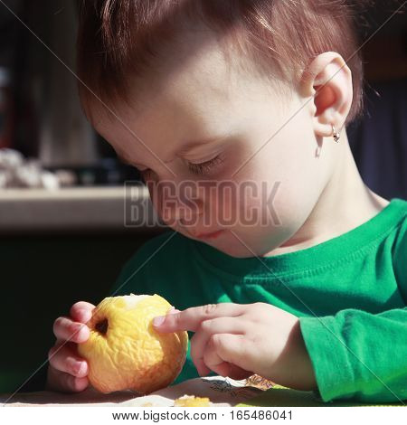 beautiful baby girl eats an apple (bio food health healthy lifestyle vegetarian food)