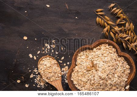 Uncooked Oat flakes in wooden bowl. Rustic style. Top view with copy space.