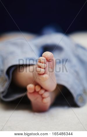 bare feet of newborn baby in jeans