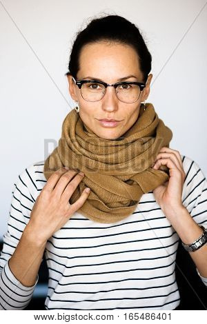 Portrait of businesswoman in glasses isolated on white. Photo of glasses made with open wide diaphragm in studio. Business lady with scarf on looking at camera.