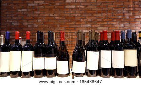 Wine shop. Closeup shot of wineshelf. Bottles lay over straw.