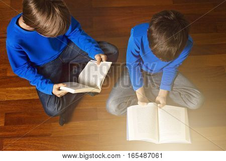 Child reading book on the floor at home. Top view