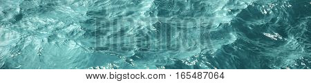 Texture blue sea water with sunny reflections, border design panoramic banner