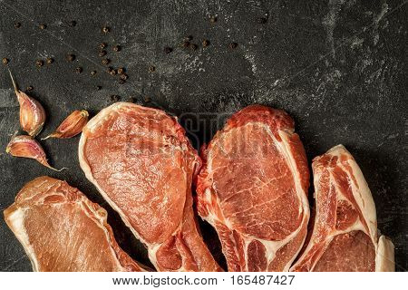 raw pork steaks on the black background close up top view copy space