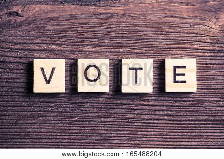 Wooden elements on wooden table spelling word vote