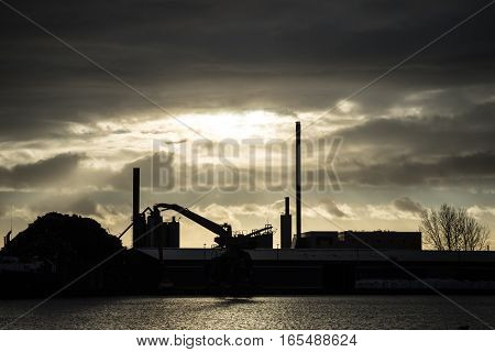 industrial port area with crane and buildings in sunset