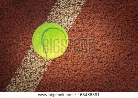 Close up of tennis ball on clay court./Tennis ball, Tennis sport, Tennis green color, Tennis concept, Play tennis, Tennis court, single tennis ball