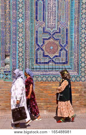 SAMARKAND, UZBEKISTAN - MAY 20, 2011: Architectural detail at the Shah-i-Zinda with traditionally dressed Uzbek women
