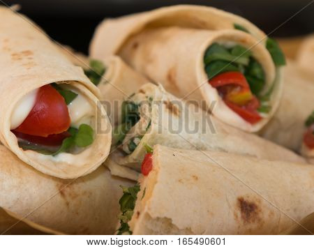 Italian Piadina Rolled And Filled With Cheese, Tomato And Argula: Typical Italian Flat Unleavened Br