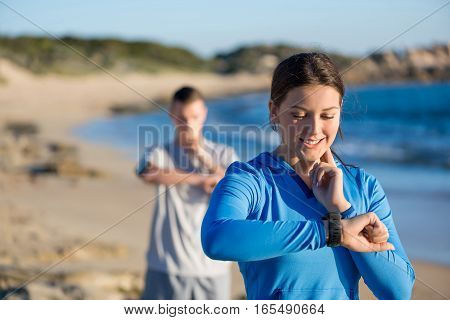 Young couple on beach checking heart rate after run