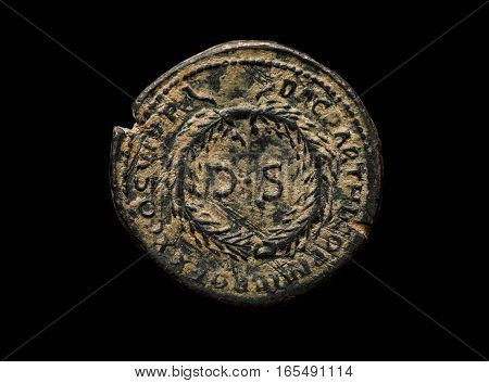Ancient Roman Bronze Coin With Ds Letters On It Isolated On Black