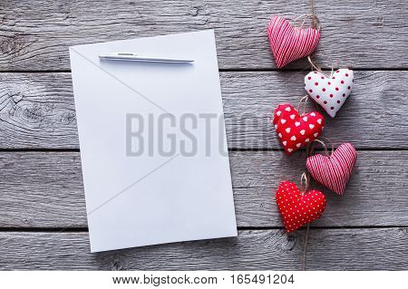 Valentine confession letter background with diy sewed pillow hearts bunch on red clothespins at rustic gray wood planks. Happy lovers day card mockup, copy space