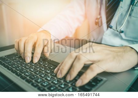 Close-up of a medical worker typing on laptop vintage tone. Doctor using laptop. Doctor using internet. Doctor using keyboard. Doctor using computer. Doctor working. Uniform doctor.