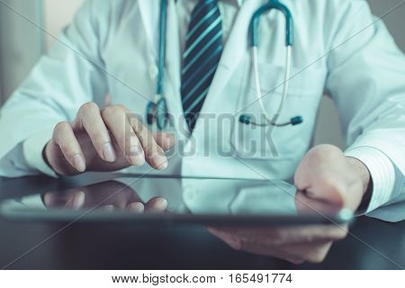 Unknown doctor using computer plane-table. doctor using tablet vintage tone. doctor using tablet concapt. doctor using tablet closeup on hand. doctor in clinic. doctor in hospital. hand docter holding tablet.