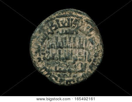 Ancient Islamic Bronze Coin With Letters On It Isolated On Black