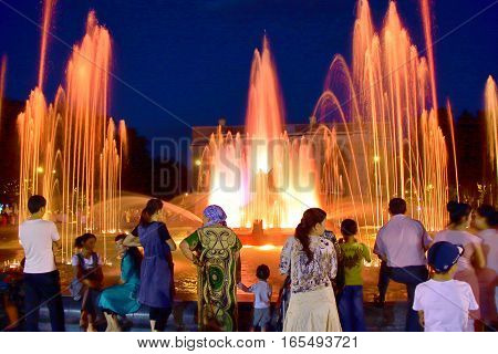 TACHKENT, UZBEKISTAN - MAY 23, 2011: Uzbek people gathering in the evening  in front of a singing fountain