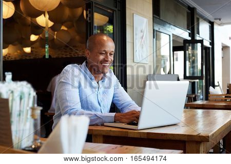 Smiling Businessman Sitting At Table With Laptop