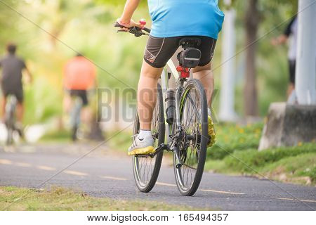 Cyclists Ride Along Bike Path In Park