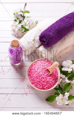 Spa setting. Sea salt in bowl towels and flowers on white wooden background. Selective focus. Place for text.Vertical image.