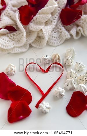 heart made of red ribbon with meringue and petals of red roses