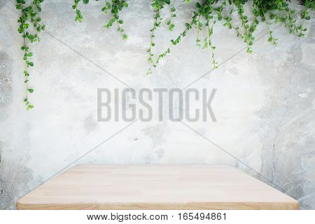Wooden table with concrete wall and ornamental plants or ivy or garden tree for background.