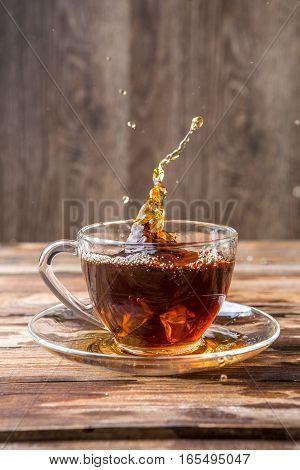 Spill tea in transparent mug on blank wooden background