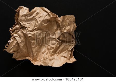 old paper, torn and crumpled like garbage, isolated on black background. Aged craft obsolete sheet with copy space, vertical