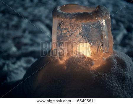 Beautiful ice lantern in peaceful winter scene. Warm candlelight in cold night.