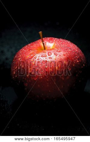 red apple with drops on dark background