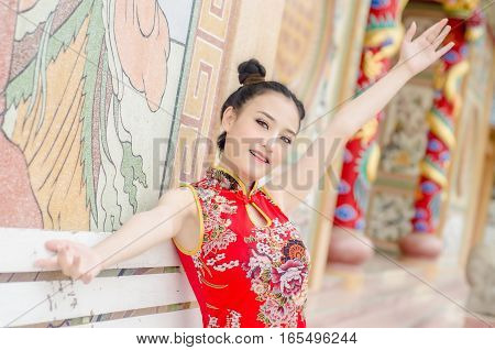 Beautiful Asian girl wear cheongsam and show something to you in chinese new year