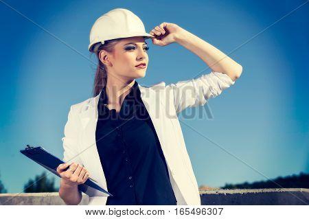 Female Engineer In Helmet In Front Of Construction Site