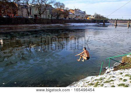 Uzhgorod Ukraine - January 19 2016: Greek-Catholic parishioner jumping into the icy river during the celebration of Epiphany in the Ortodox tradition.