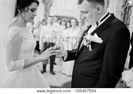 Groom Puts A Wedding Ring On Hand Of Bride At Hall Of Registration Their Marriage. Black And White P