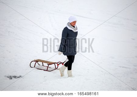 GRODNO BELARUS -JANUARY 15 : Girl with a sled up the hill rises in the winter JANUARY 15 2016 GRODNO BELARUS