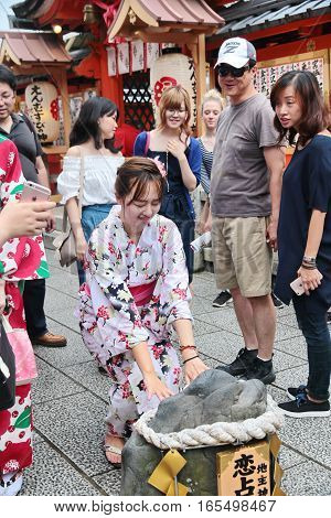 KyotoJapan-June 262016 Women's kimono closed eyes and try walk to Stone lots of love belief. After the blessing love So true at the Jishu Jinja shrinewithin Kiyomizu-dera temple in Kyoto Japan
