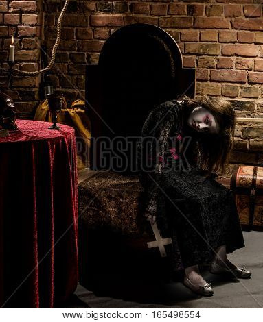 Little girl vampire sitting on the chair with christ cross in hands