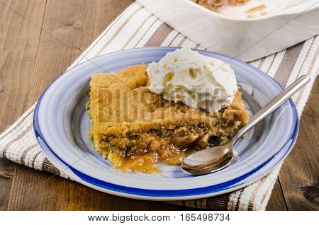 rhubarb crumble cake with whipped cream and spoon on a plate