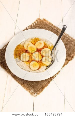 creamy breakfast porridge with syrup and banana slice in a deep plate