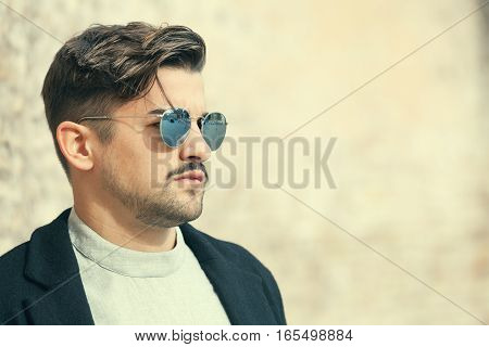 Cool handsome fashion young man. Stylish man with sunglasses. Confident attitude and fashionable clothes