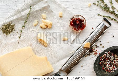 Parmesan piece closeup with small grater and various herbs and seasoning, rosemary and pepper. Classic italian cuisine cooking ingredients, grated hard cheese. Top view
