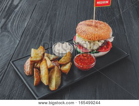 Fast food restaurant dish on served table. Meat steak medium rare in cheese burger, potato chips and wedges. Dish on dark black wood background. Hamburger, mayonnaise and spicy tomato sauce. Filtered