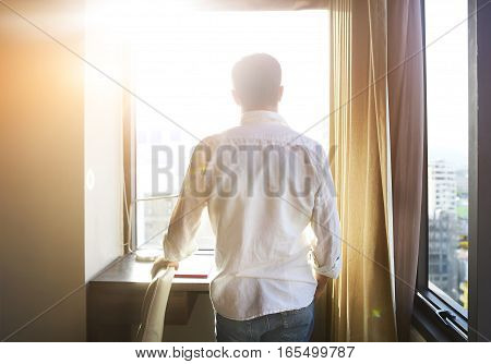 Rear view of young man looking at dawn city scenery in window after waking up.