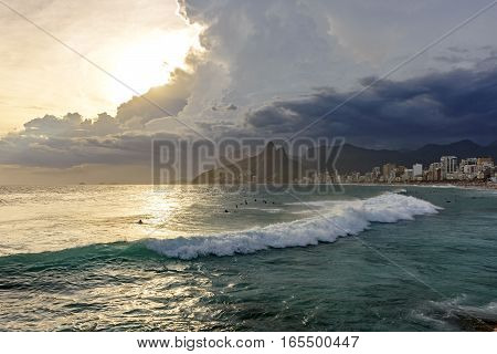 Arpoador beach in Rio de Janeiro with its stones buildings and the seaside during sunset and the Two Brothers hill in background